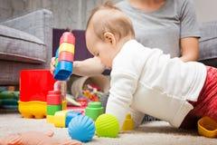 Nove meses de bebê idoso que joga com seus brinquedos Fotografia de Stock Royalty Free