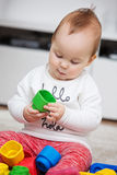 Nove meses de bebê idoso que joga com seus brinquedos Imagem de Stock