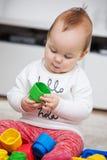 Nove mesi della neonata che gioca con i suoi giocattoli Immagine Stock
