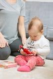 Nove mesi della neonata che gioca con sua madre Fotografie Stock Libere da Diritti