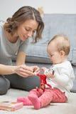 Nove mesi della neonata che gioca con sua madre Fotografia Stock