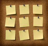 Nove note gialle appuntate alla priorità bassa del sughero del grunge Immagini Stock