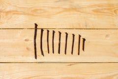 Nove pregos em uma tabela de madeira Imagens de Stock