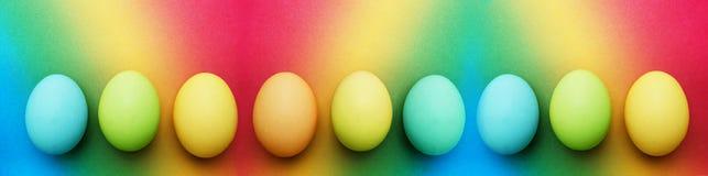 Nove uova di Pasqua gialle verde mela del turchese blu organico biologico su un fondo dell'arcobaleno immagine stock