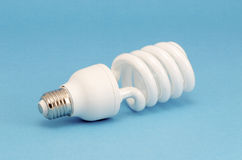 Novel fluorescent light bulb on blue background Royalty Free Stock Image