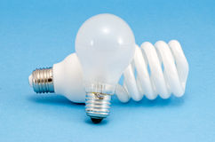 Novel fluorescent lights incandescent heat bulb. Novel fluorescent lights and old incandescent heat bulb on blue background. New technology for less electricity stock images