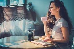 Novela bonita da leitura da senhora em um café fotografia de stock royalty free
