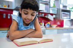 A novela da leitura da menina com braços cruzou-se na cozinha foto de stock