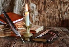 Novela da pena e do livro perto de uma vela Imagens de Stock Royalty Free
