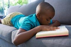 Novela de la lectura del muchacho mientras que miente en el sofá en casa fotografía de archivo libre de regalías