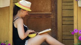 Novela de la lectura de la mujer joven y fresas de la consumición metrajes