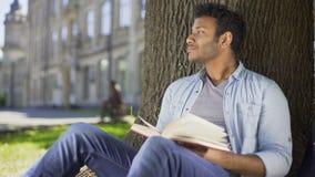 Novela favorita da leitura masculina sob a árvore, pressionando o livro contra a caixa, sonhando acordado video estoque
