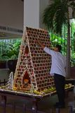 Man building large gingerbread house in a commercial setup royalty free stock photo