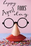 Novelty glasses and text happy april fools day. A pair of fake eyeglasses, with nose and mouth, and the text happy april fools day, on a rustic surface full of Stock Photography