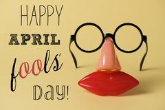 Novelty glasses and text happy april fools day. A pair of fake eyeglasses, with nose and mouth, and the text happy april fools day, on a yellow background Stock Photos