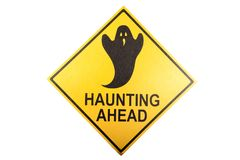 A haunting sign for the Halloween holiday. A novelty haunting ahead ghost sign isolated against a white background Stock Photos