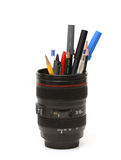 Novelty pencil holder. Image of a novelty pencil holder shaped like a Canon lens, holding an assortment of pencils and pens Royalty Free Stock Photos