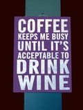 A novelty sign suggesting that Coffee will keep you busy until its time to drink wine Royalty Free Stock Photography