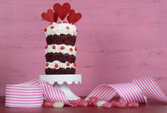 Novelty triple layer red velvet cupcake. On white cake stand with ribbons and candy against a vintage shabby chic pink and red wood background Royalty Free Stock Image