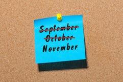 November-Anfang und September, Oktober-Endenkonzept geschrieben am Papier festgesteckt zur KorkenAnschlagtafel Büro, Geschäft Stockbild