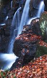 November Falls. Long exposure capture of Waterfall as Twigs Leaves and Icicle's cling to soaked Boulders on a freezing November day in Northumberland, England Royalty Free Stock Photo