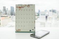 November kalender med smartphonen för möte och tidsbeställning Arkivbilder