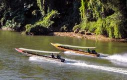 November 2018 - Kanchanaburi, Thailand - zwei Boote des langen Schwanzes steuern den Fluss Kwai lizenzfreie stockfotos
