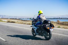Motorcyclist riding on a highway, San Francisco bay area royalty free stock photography