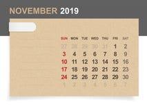 November 2019 - Monatskalender auf Hintergrund des braunen Papiers und des Holzes lizenzfreie abbildung