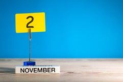 November 2nd Dag 2 av den november månaden, kalender på arbetsplats med blå bakgrund Höst Time Tomt avstånd för text Royaltyfri Foto