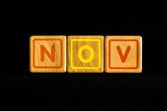 November på wood kubik på svart bakgrund arkivfoto
