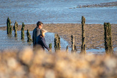 20 November, 2015, Pett, Uk, Man and woman walking along a winter beach Royalty Free Stock Photography