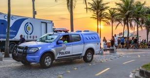 26 November 2016 Polisbil på bakgrunden av den härliga solnedgången med den orange solen i den Ipanema stranden, Rio de Janeiro,  royaltyfri fotografi