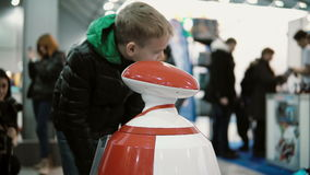 NOVEMBER 5, 2016 RUSSIA, MOSCOW Robotics Expo. Humanoid autonomous robot looking at little boy and speak with him. 4K stock footage