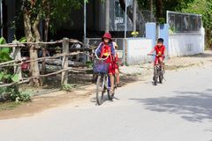 November 2018, School children boy girls uniform cycling village street, Vietnam stock photo