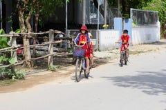 November 2018, Schoolkinderen eenvormige het cirkelen dorpsstraat, Vietnam stock foto
