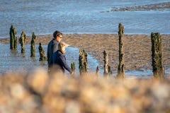 20. November 2015 setzen Pett, Großbritannien, Mann und Frau, die entlang einen Winter gehen auf den Strand Lizenzfreie Stockfotografie