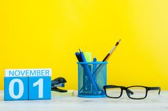 November 1st dag 1 av månaden, träfärgkalender på gul bakgrund med kontorstillförsel Höst Time Arkivbild