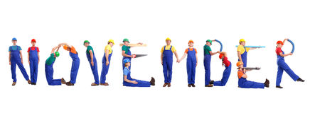 November staff. Group of young people wearing different color uniforms and hard hats forming November word - isolated on white background - calendar concept royalty free stock photos