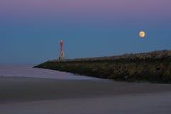November super full moon rising over ocean jetty Royalty Free Stock Image