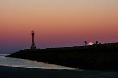 November super full moon rising over ocean jetty Royalty Free Stock Images