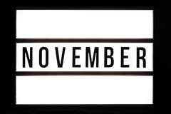 NOVEMBER text in a light box. Isolated over a black background stock images