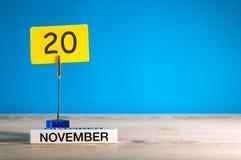 November 20th Dag 20 av den november månaden, kalender på arbetsplats med blå bakgrund Höst Time Tomt avstånd för text Arkivfoto