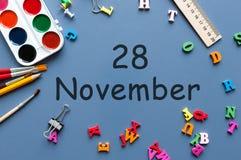 November 28th Dag 28 av den sista höstmånaden, kalender på blå bakgrund med skolatillförsel Att ta för kvinna och för manar noter Royaltyfria Bilder