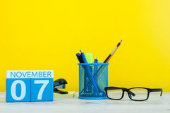 November 7th Dag 7 av månaden, träfärgkalender på gul bakgrund med kontorstillförsel Höst Time Arkivbilder