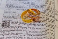 november 04 2016 Trouwringen plaatst op een open Bijbel aan een vers in het boek van Ontstaanhuwelijk royalty-vrije stock fotografie