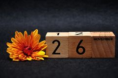 26 November on wooden blocks with an orange daisy. On a black background royalty free stock images