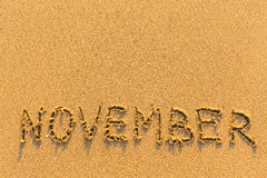 November - word inscription on the gold sand beach. Royalty Free Stock Images