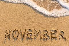 November - Wort gezeichnet auf den Sandstrand mit der weichen Welle Lizenzfreie Stockfotos
