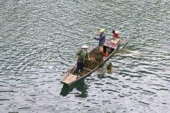 Novembre 2018, la gente che raccoglie la barca di fiume del figlio delle piante dell'erbaccia, Phong Nha, Vietnam fotografia stock